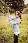 Smiling woman touching apple tree
