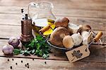 An arrangement of porcini mushrooms, oil, parsley, garlic and pepper