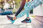 Cropped shot of female runner stretching legs on sidewalk