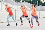 Three female runners racing at city stairway