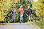 Three female runners running along park path
