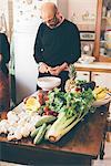 Senior man slicing artichokes at kitchen table