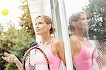 Mature female tennis player leaning against patio door