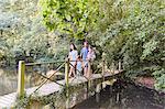 Family crossing footbridge in park with trees