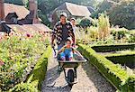 Father pushing daughter in wheelbarrow in sunny garden