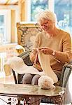 Smiling senior woman knitting scarf
