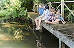 Family relaxing on footbridge over pond