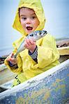 Young boy wearing raincoat holding a mackerel, portrait.