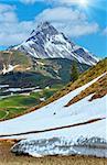 Summer mountain view to Biberkopf mount, snow thawing meadow, and sunshine in blue sky (Warth, Vorarlberg, Austria).