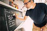 Close-up of vendor writing menu on blackboard at food truck
