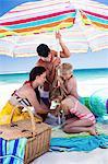 Cute family setting their umbrella on the beach