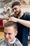 Young man in barbershop having haircut, smiling