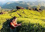 Young woman looking at tea plants in tea plantations near Munnar, Kerala, India
