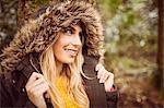 Beautiful blonde woman wearing hooded jumper in the woods