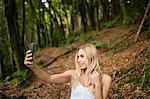 Beautiful blonde woman taking selfie in the woods