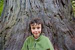 Boy in front of tree trunk, portrait