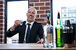 Businessman drinking blue shots in a pub