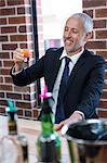Businessman drinking orange shots in a pub