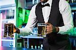 Bartender serving two glasses of beer at bar counter in bar