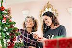 Mature woman and daughter decorating Xmas tree
