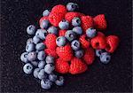 Blueberries and raspberries on black.