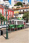 Old green tram arriving at Largo das Portas do Sol, Alfama District, Lisbon, Portugal