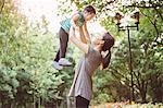 Pretty mom & child playing joyfully in park