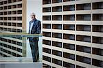 Portrait serious businessman standing on walkway in modern office
