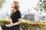 Pensive businesswoman on sunny urban balcony