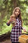 Girl holding mushroom in forest