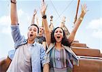 Portrait enthusiastic friends cheering on amusement park ride