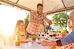 Man serving salad at sunny patio table