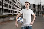 Teenage boy holding football in his underarm, Bavaria, Germany
