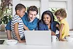 Happy multi-ethnic family using laptop