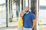 Portrait of couple on beach below wooden pier