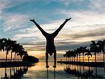 Mature man balancing on poles, dusk, South Pointe Park, South Beach, Miami, Florida, USA