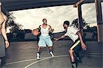 Young men playing basket ball on basket ball court smiling