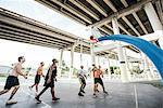 Men on basketball court watching basketball go through hoop