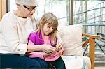 Senior woman and granddaughter knitting on living room sofa