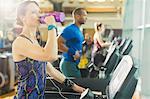 Woman on treadmill drinking water