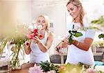 Smiling florists arranging bouquet in flower shop
