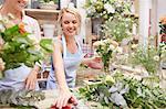 Smiling florist arranging bouquet in flower shop