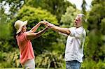 Senior couple enjoying while dancing in yard