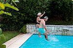 Senior couple jumping in swimming pool at yard
