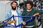 Hipster bike mechanic holding a bike piece