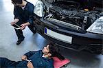 Mechanics repairing car