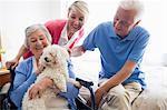 Senior couple and nurse taking care of a dog