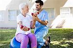 Nurse helping senior woman doing exercices