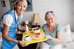 Nurse giving food to a senior woman