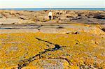 Man walking along rocky coastline